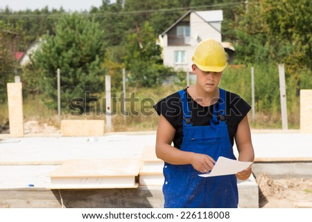 Builders checking specs or an order of building materials as he stands on site in his hardhat and overalls - stock photo