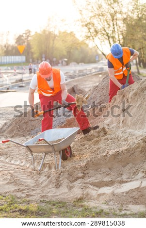 Builders on construction site pouring heavy sand into the barrow - stock photo
