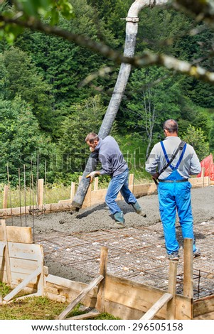 Builders pouring cement on a small construction site - stock photo