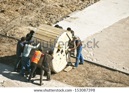builders pushing the cable bobbin. - stock photo