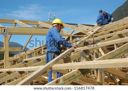 builders working on the roof of a large house - stock photo
