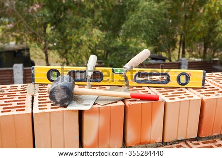 Building a brick wall. Bricklaying instrument (spatula, construction level and industrial hammer) - stock photo