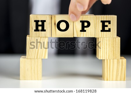 Building a bridge of wooden cubes with word hope written on them. Inspiration concept. - stock photo