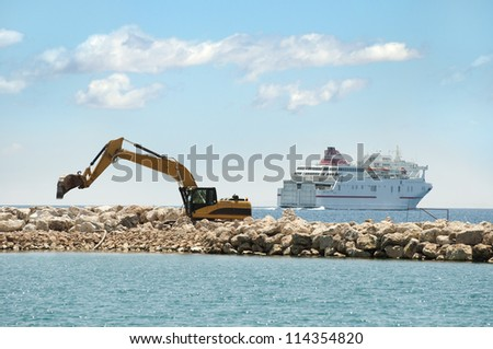 Building a dike. Excavator put stones in the sea. A ship on background - stock photo