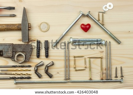 Building a house for the family. Plans to build a small house. Architect designing a house for a young family. House from nails and screws. Needed for building. Ideas about building a house. - stock photo
