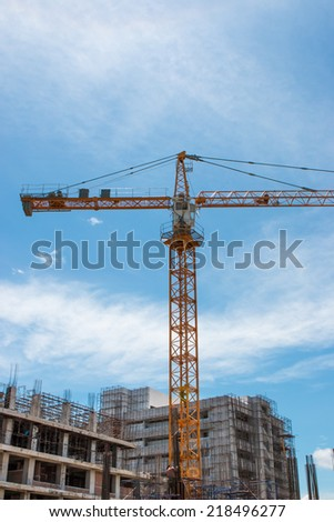 building and crane under construction against blue sky