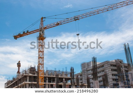 building and crane under construction against blue sky  - stock photo