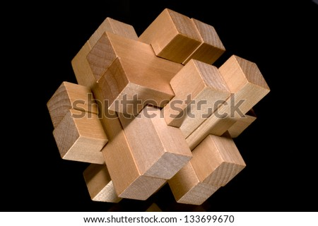 Building blocks forming a challenging puzzle isolated on a black background - stock photo