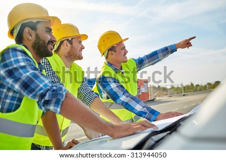 building, construction, development, teamwork and people concept - close up of builders in hardhats and high visible vests with blueprint on car hood - stock photo