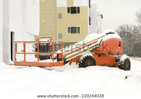 Building construction equipment sit idle during a winter snow and freezing rain storm - stock photo