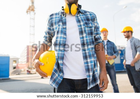 building, construction, protective gear and people concept - close up of builder holding yellow hardhat or helmet outdoors