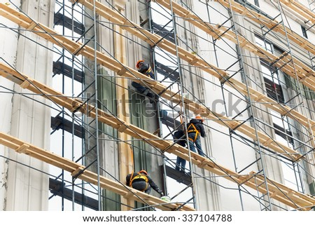 Building construction with scaffolding. Painting works at height