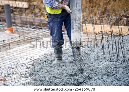 building construction worker pouring cement or concrete with pump tube  - stock photo