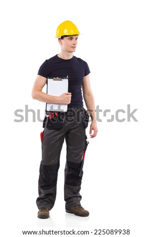 Building contractor. Construction worker in yellow helmet standing and holding clipboard under his arm. Full length studio shot isolated on white. - stock photo