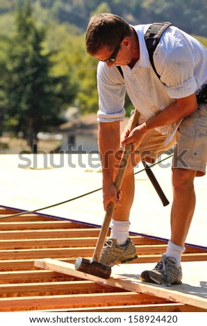 Building contractor putting down subfloor over the floor joist for a second story on an new commercial housing apartment. - stock photo