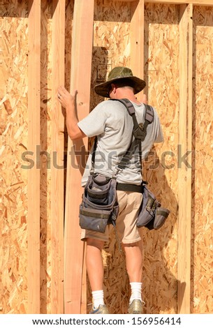 Building contractor worker putting in a interior wall partition nailer wall for the first floor on a new home construction project - stock photo