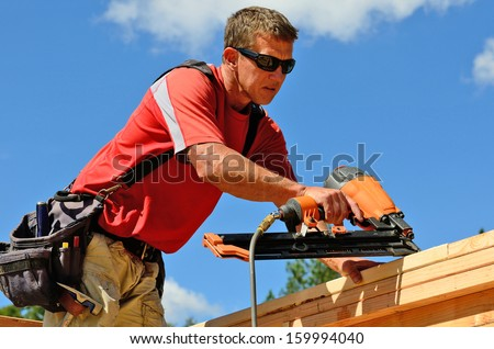 Building contractor worker with a air nail gun  nailer working on the corner of the top plate of the first floor walls on a new home construciton project - stock photo
