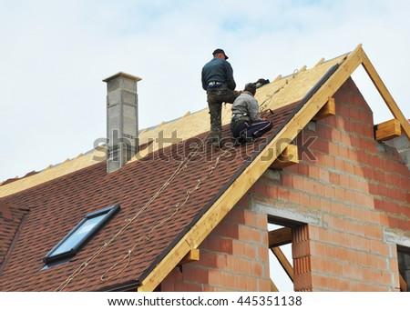 Building contractors putting the asphalt roofing. Roofers laying tiles on the roof while roofing a house outdoor. Roofers Install, Repair Asphalt Shingles or Bitumen Tiles on the Rooftop Outdoor. - stock photo