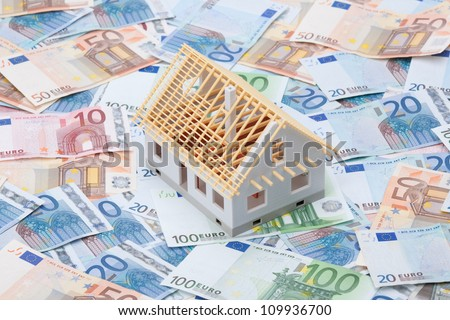 Building cost (construction cost) concept. Model of house under construction (rough construction) and money. - stock photo