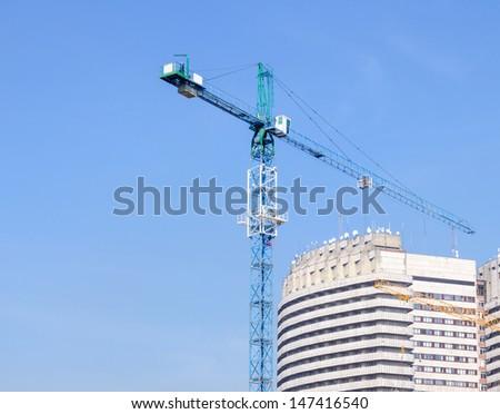 building crane against blue sky - stock photo