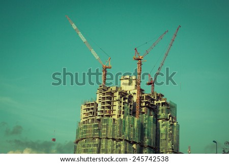 Building crane and building under construction - stock photo