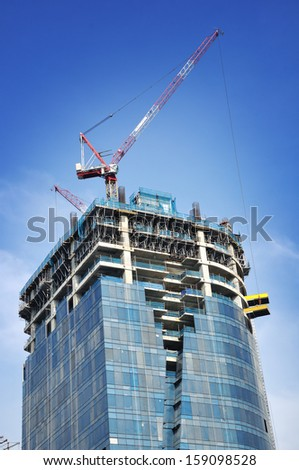 Building crane and building under construction against blue sky. - stock photo