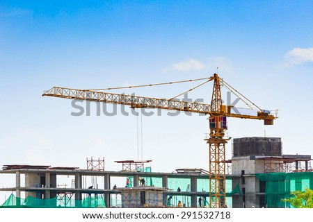 Building crane and construction site under blue sky - stock photo