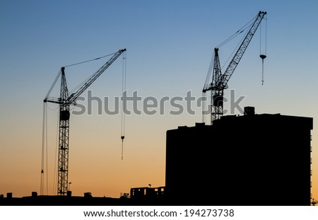 building crane on a background of a building under construction. on sunset background  - stock photo