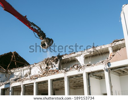 Building demolition by a heavy  twisted rebars industrial machine  - stock photo