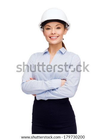 building, developing, consrtuction and architecture concept - friendly young smiling businesswoman in white helmet - stock photo