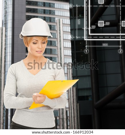 building, developing, consrtuction, architecture concept - female contractor in white helmet with blueprint