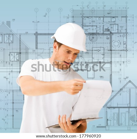 building, developing, construction and architecture concept - male architect in helmet looking at blueprint - stock photo