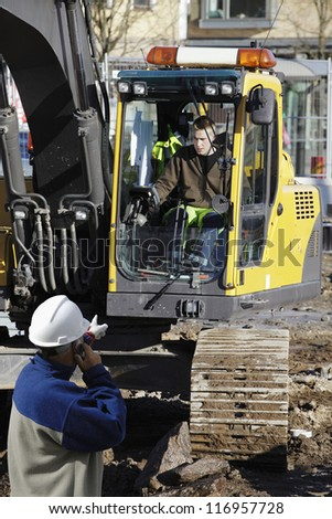 building engineer directing bulldozer, digger, inside construction site - stock photo