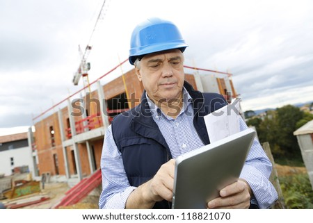 Building entrepreneur using digital tablet - stock photo