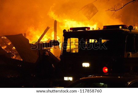 Building fire with fire engine, smoke and heavy flame. - stock photo