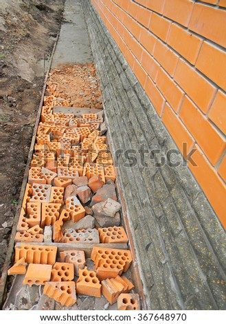 Building foundation waterproofing.  New construction waterproofing basement walls from outside with detail of a pavement to walk. - stock photo