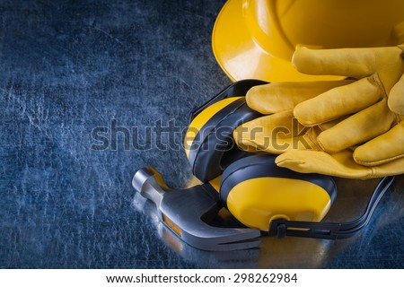 Building helmet earmuffs leather safety gloves and claw hammer on scratched metallic background construction concept. - stock photo