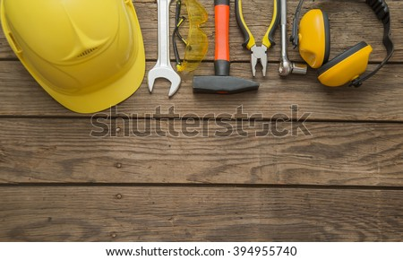 Building helmet safety glasses pliers tin snips on wooden background. personal safety accessories on surface. Items include a hard hat with ear protection attached, safety goggles, hammer, wrenches