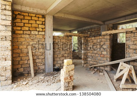 building house of concrete frame with walls from shell rock - stock photo