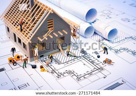 building house on blueprints with worker - construction project  - stock photo