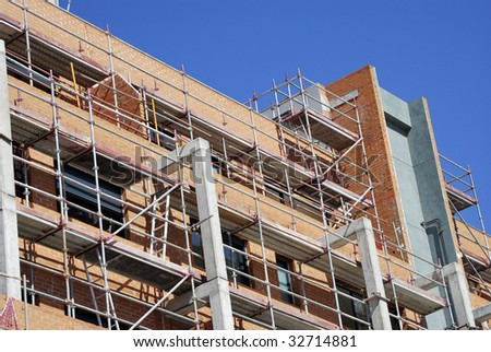 Building in construction with scafolds for security