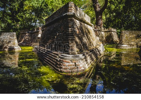 building in ruins on a green swamp with water - stock photo