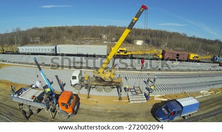 Building machines and crane with sleepers at construction of new railway next to wagons, aerial view - stock photo