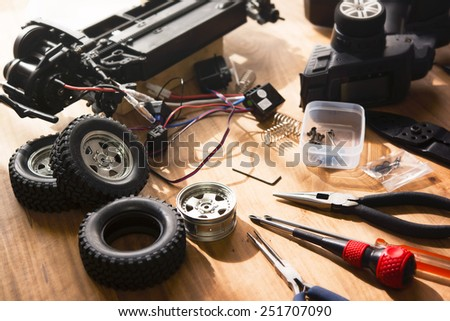 Building model cars. Radio control car assembly scene, RC car assembly on wooden work desk and tools. Natural lighting. - stock photo