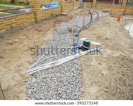 Building new concrete pavement for garden pathway. Foundation for paving with electrical wires and watering equipment garden, irrigation supplies. - stock photo