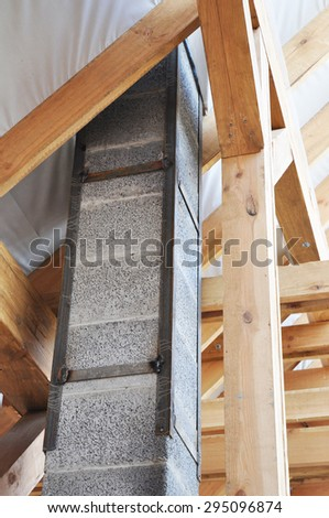 Building new modular pumice stone chimney inside  of roof construction.  - stock photo