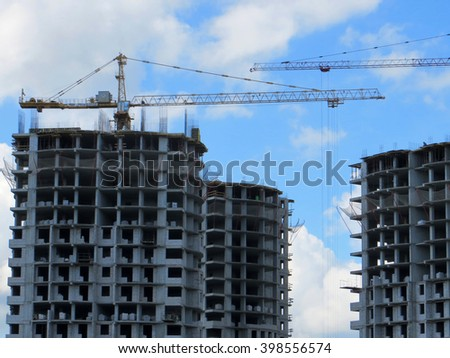 Building of a modern residential apartment complex with tower cranes against a blue sky - stock photo