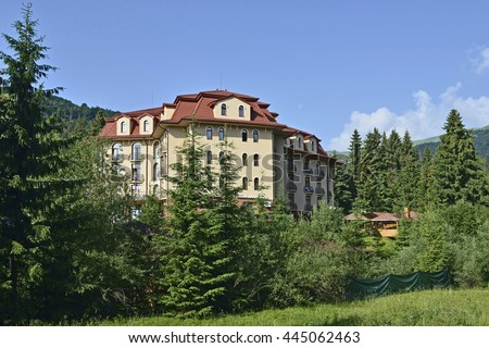 Building of Hotel in green fir forest under blue sky