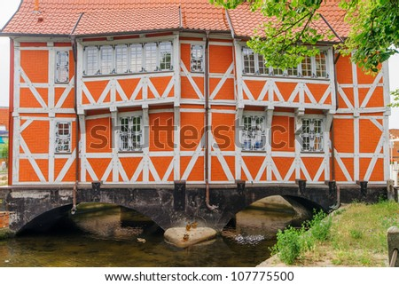 Building on bridge in historic Wismar, a Hanseatic League town in Northern Germany on the Baltic Sea, with elegant building styles from 14th-century Gothic to 19th-century Romanesque revival. - stock photo