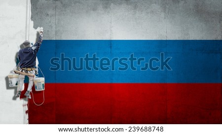 Building Painter hanging from harness painting a wall in with red and blue colors - stock photo